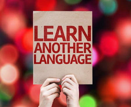 another: Hands holding cardboard with Learn Another Language on bokeh background