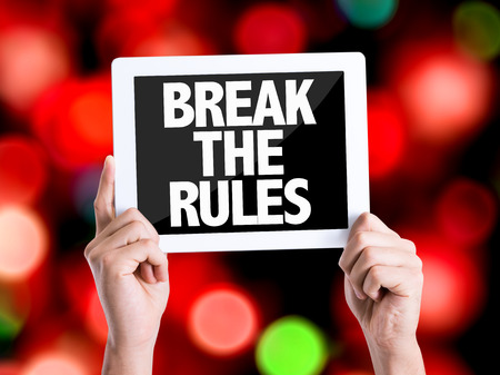 break the rules: Hands holding cardboard with Break The Rules on bokeh background