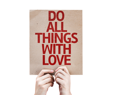 gentleness: Hands holding cardboard with Do All Things With Love on white background