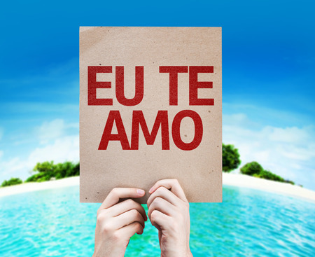 express feelings: Hands holding cardboard with I Love You in Portuguese on island background Stock Photo