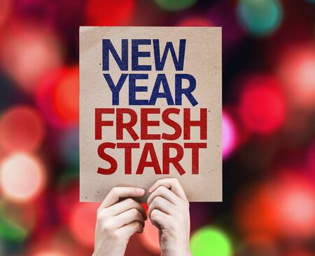 fresh start: Hands holding cardboard with New Year Fresh Start on bokeh background Stock Photo