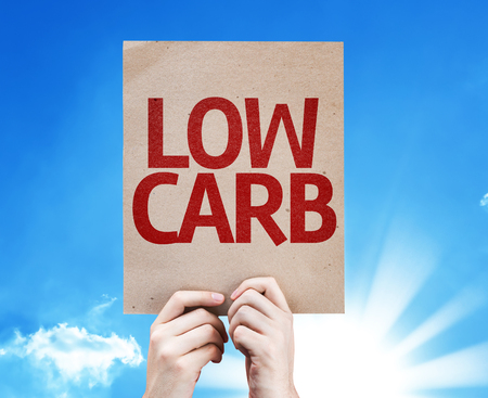 carb: Hands holding cardboard with Low Carb on sunny background Stock Photo