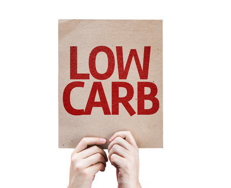 carb: Hands holding cardboard with Low Carb on white background