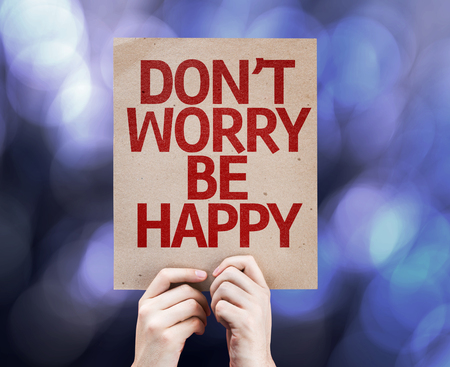 dont worry: Hands holding cardboard with Dont Worry Be Happy on bokeh background