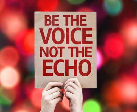 Handen die karton met Be The Voice Niet The Echo op de achtergrond bokeh