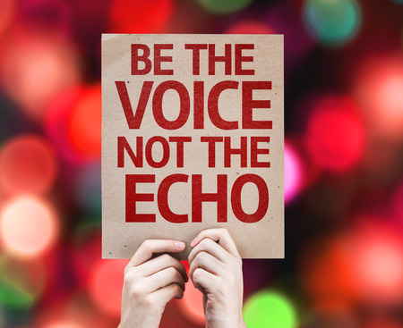 echo: Hands holding cardboard with Be The Voice Not The Echo on bokeh background