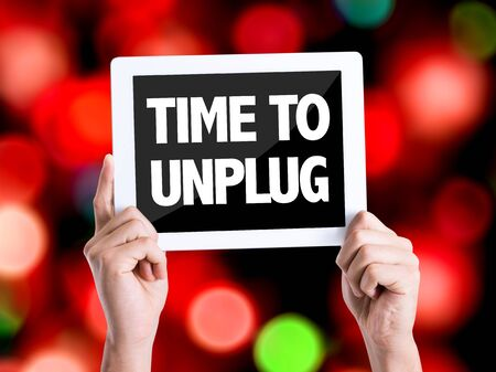 unplug: Hand holding tablet pc with Time to Unplug on bokeh background
