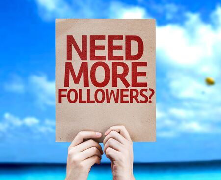 followers: Hand holding cardboard with Need More Followers on sea background Stock Photo