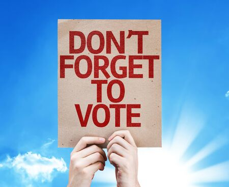 Hand holding cardboard with Don't Forget To Vote on sunny background
