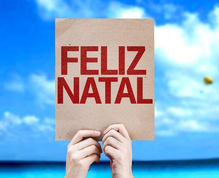 natal: Cardboard with text Feliz Natal on sky background Stock Photo