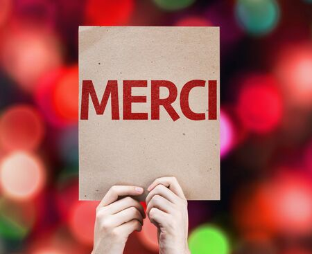 thankfulness: Hand holding cardboard with Thank You in French on bokeh background