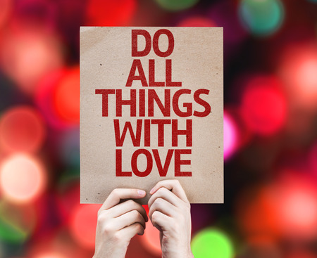 gentleness: Hand holding cardboard with Do All Things With Love on bokeh background Stock Photo
