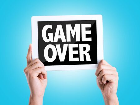 the game is over: Tablet pc with Game Over text on blue background