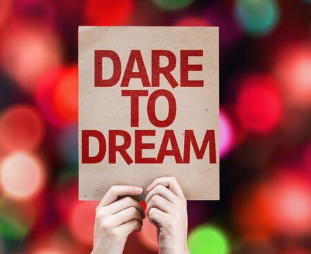 Cardboard with Dare to Dream text on bokeh background Stock Photo