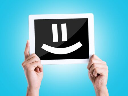 smile icon: Tablet pc with smiley face on blue background