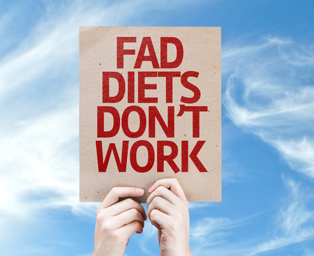 fad: Cardboard with Fad Diets Dont Work text on a sky background