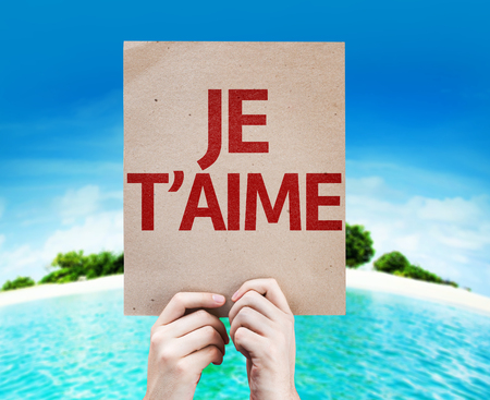 french text: Cardboard with French text of I Love You on an island background Stock Photo