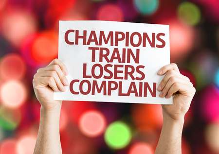 complain: Hands holding Champions Train Losers Complain card with colorful background with defocused lights