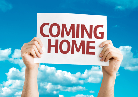 coming home: Hands holding Coming Home card with sky background Stock Photo