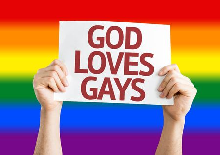 Hands holding God Loves Gay card with Rainbow flag background Stock Photo
