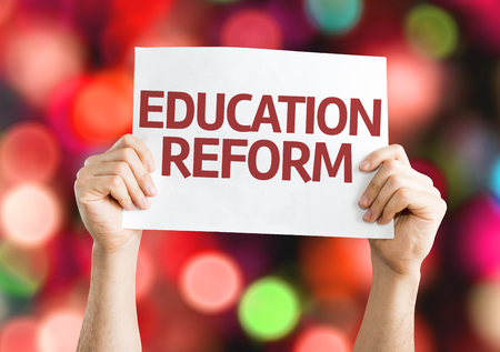 reform: Hands holding Education Reform card with colorful background with defocused lights