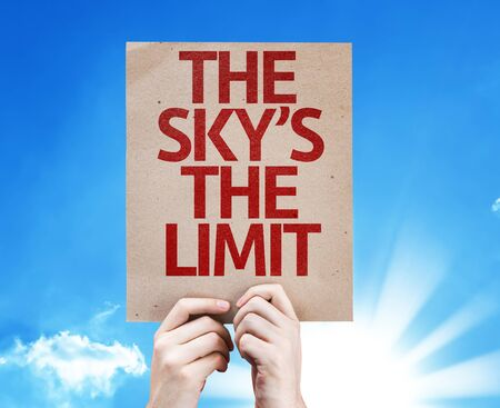 sky is the limit: Hands holding The Skys The Limit card with sky background