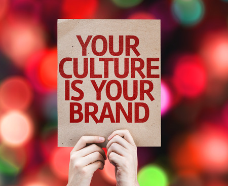 identidad cultural: Hands holding Your Culture is Your Brand card with colorful background with defocused lights Foto de archivo