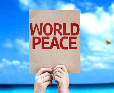 non violence: Hands holding World Peace card with a beach on background