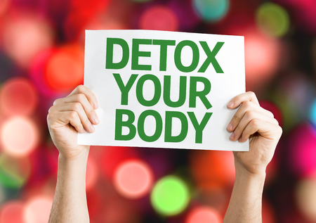 detoxification: Hands holding Detox Your Body card with colorful background with defocused lights