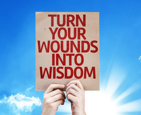Hands holding Turn Your Wounds Into Wisdom card with sky background