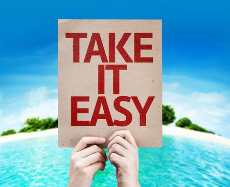 take it easy: Hands holding Take It Easy card with island background Stock Photo