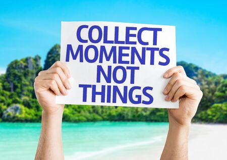 recoger: Manos que sostienen la tarjeta Momentos recoge no cosas con el fondo de la isla