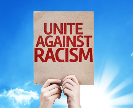 uniting: Hands holding Unite Against Racism card with sky background