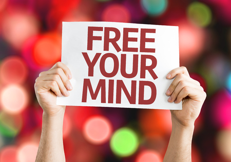 free your mind: Hands holding Free Your Mind card with colorful background with defocused lights