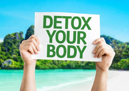 Handen die Detox Your Body kaart met eiland achtergrond