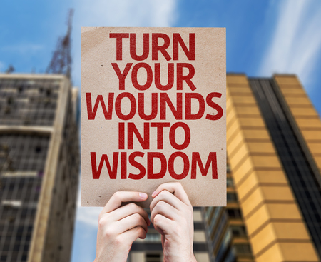 Hands holding Turn Your Wounds Into Wisdom card with urban background Banco de Imagens - 56224900