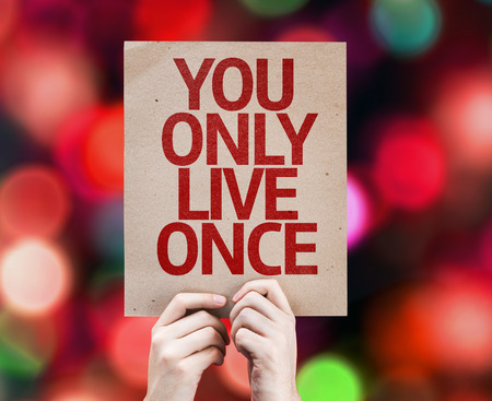 cardboard only: Hands holding You Only Live Once card with bokeh background Stock Photo