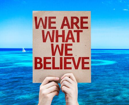 we: Hands holding We Are What We Believe card with sea background