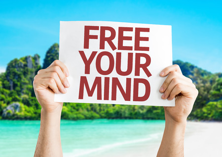 free your mind: Hands holding Free Your Mind card with beach background