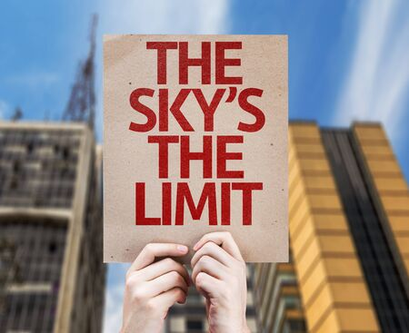 city limit: Hands holding The Skys The Limit card with city background Stock Photo