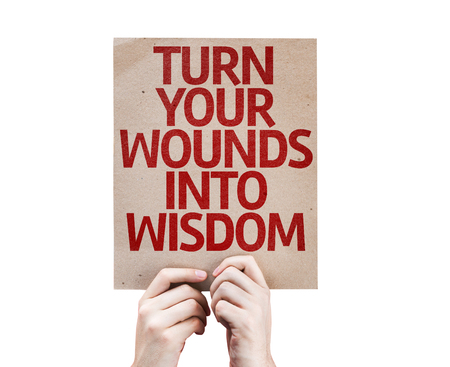 learned: Hands holding Turn Your Wounds Into Wisdom card isolated on white