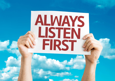 always listen first: Hands holding Always Listen First card with sky background Stock Photo