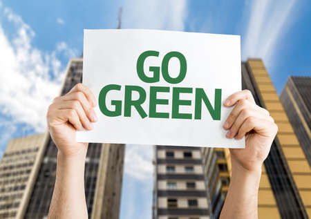 go green background: Hands holding card with text: Go Green on city background