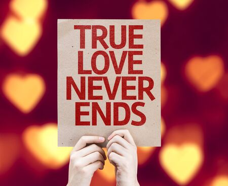 the ends: Hands holding True Love Never Ends card with heart bokeh background Stock Photo