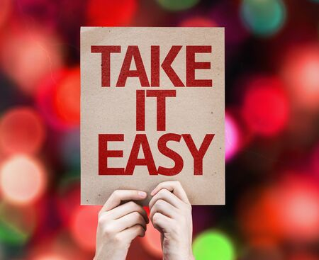 take it easy: Hands holding Take It Easy card with bokeh background Stock Photo