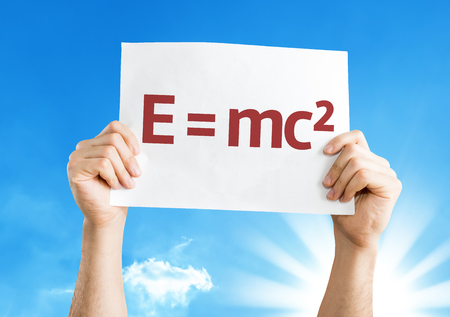 mc2: Hands holding E = mc2 card with a beautiful day