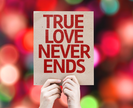 the ends: Hands holding True Love Never Ends card with bokeh background Stock Photo