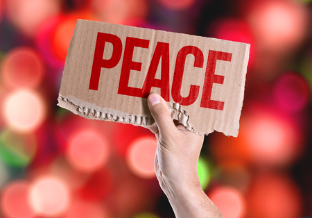 traquility: Hands holding Peace card with bokeh background