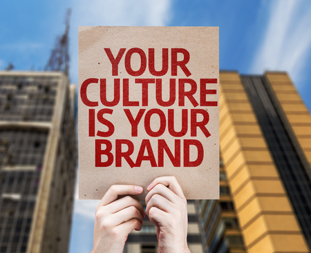 identidad cultural: Hands holding Your Culture is Your Brand card with city background