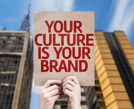 identidad cultural: Manos que sostienen su cultura es su tarjeta de la marca de fábrica con el fondo de la ciudad